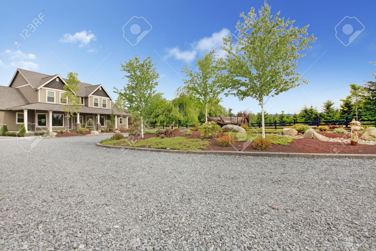 Large farm country house with gravel driveway and green landscape. - 17848846