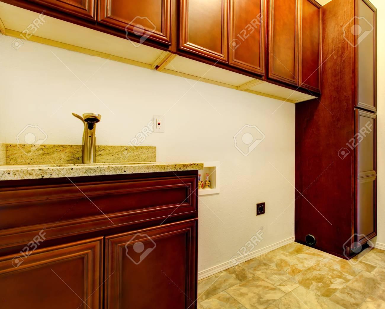 Nuova vuoto lavanderia con armadi in legno lavabo e pavimento di