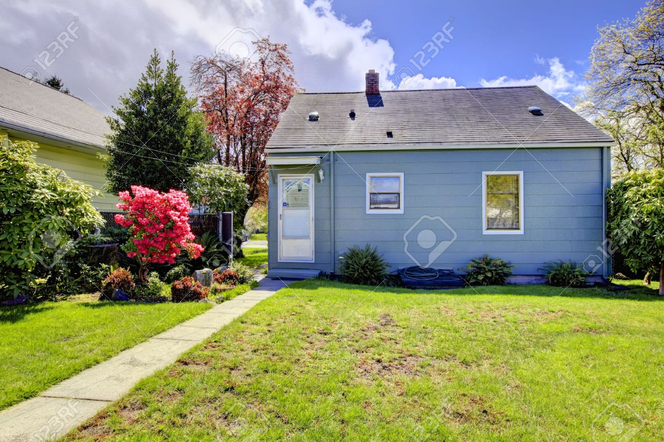 Blue small house with spring landscape from backyard with green grass.  American house build in - Blue Small House With Spring Landscape From Backyard With Green