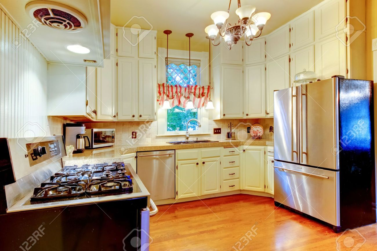 large white kitchen in an old american house with hardwood floor