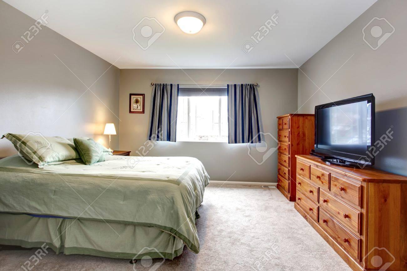 Große Graue Schlafzimmer Mit Kommode, Fernseher Und Blaue Vorhänge ...