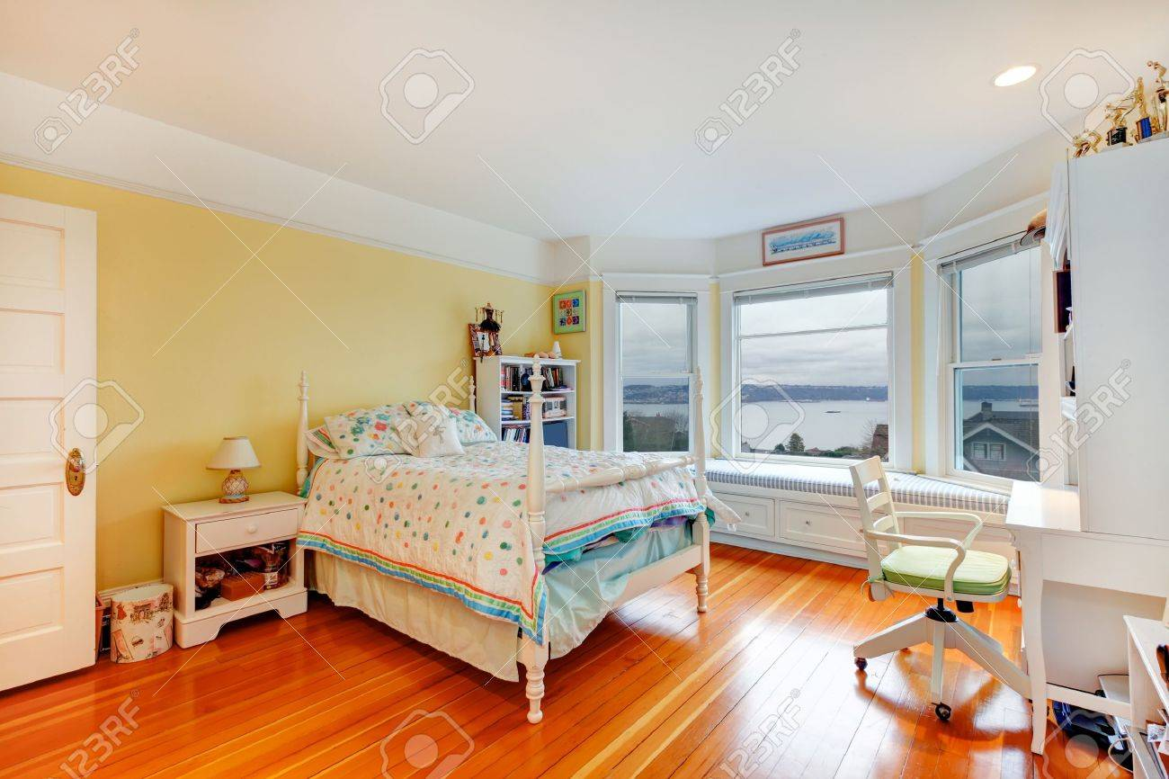 tennage girl yellow bedroom interior with white furniture and