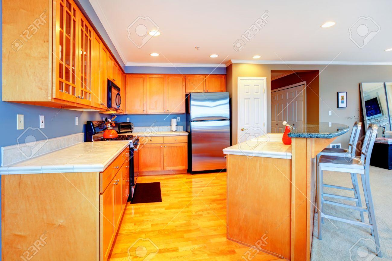 Città appartamento arancione cucina in legno con sgabelli da bar