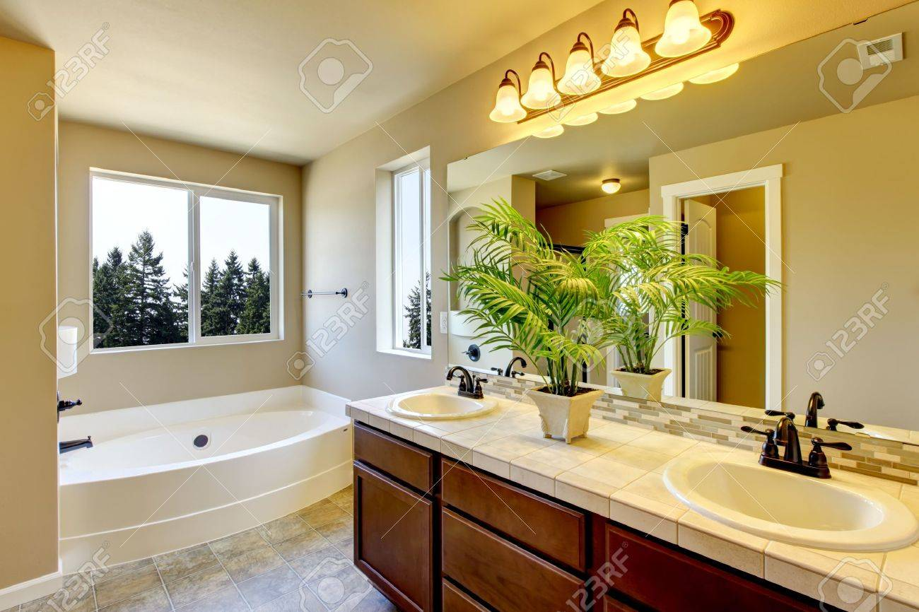 New home bathroom  interior with shower and bath combination, wood cabinet and toilet. Stock Photo - 21728644