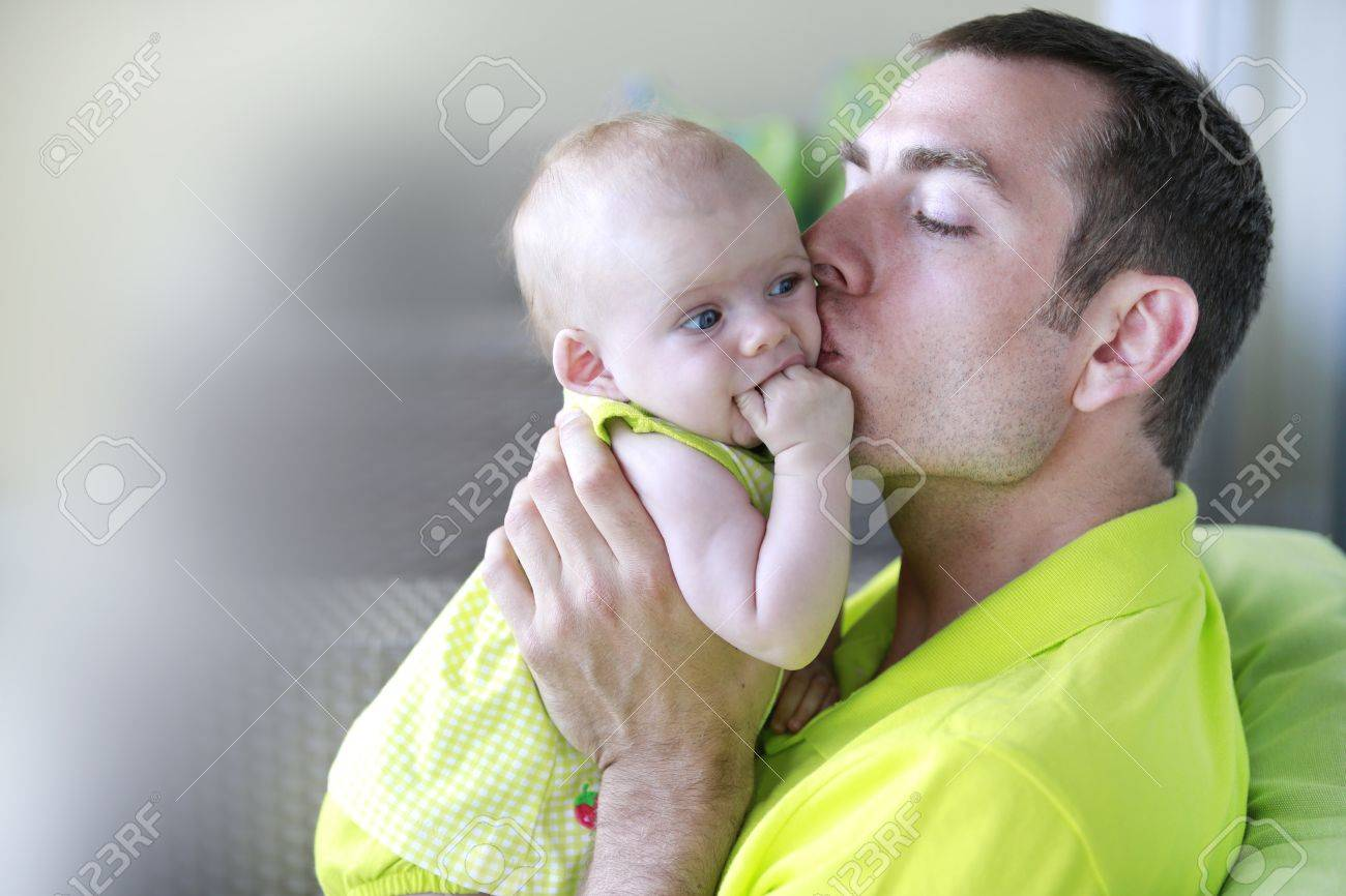 Young father is kissing baby girl. baby girl. Stock Photo - 21573734