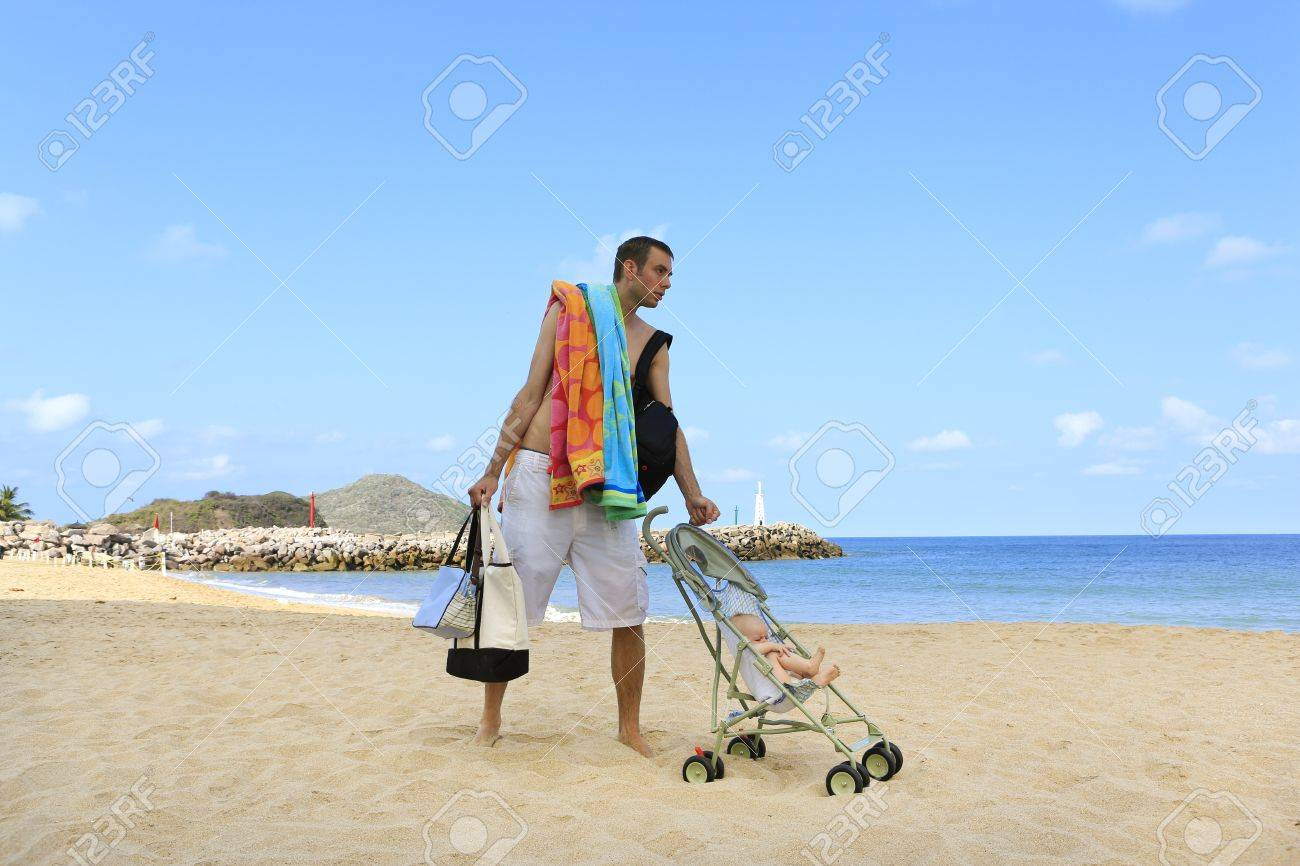 Hands full during vacation with baby  Young father is dragging stroller with little baby on the sandy beach near ocean Stock Photo - 21717742