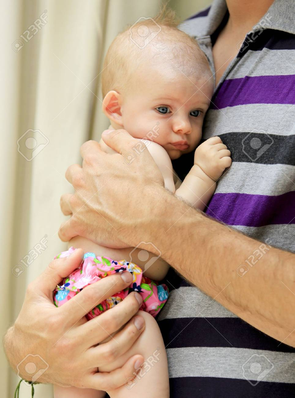 Three months old baby girl is held by her daddy near pool during vacation Stock Photo - 21729113