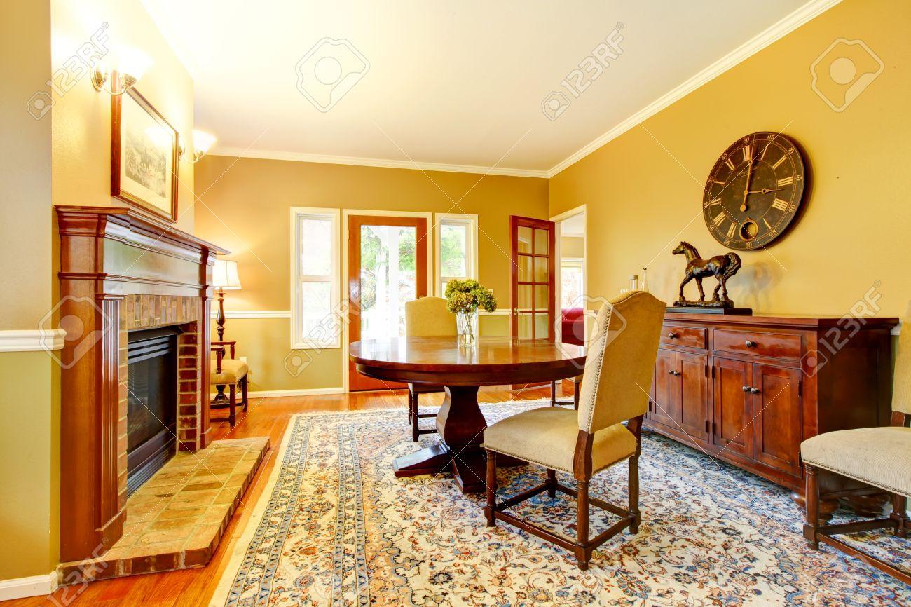 Woonkamer met open haard, mosterd muur kleur en mooi tapijt ...