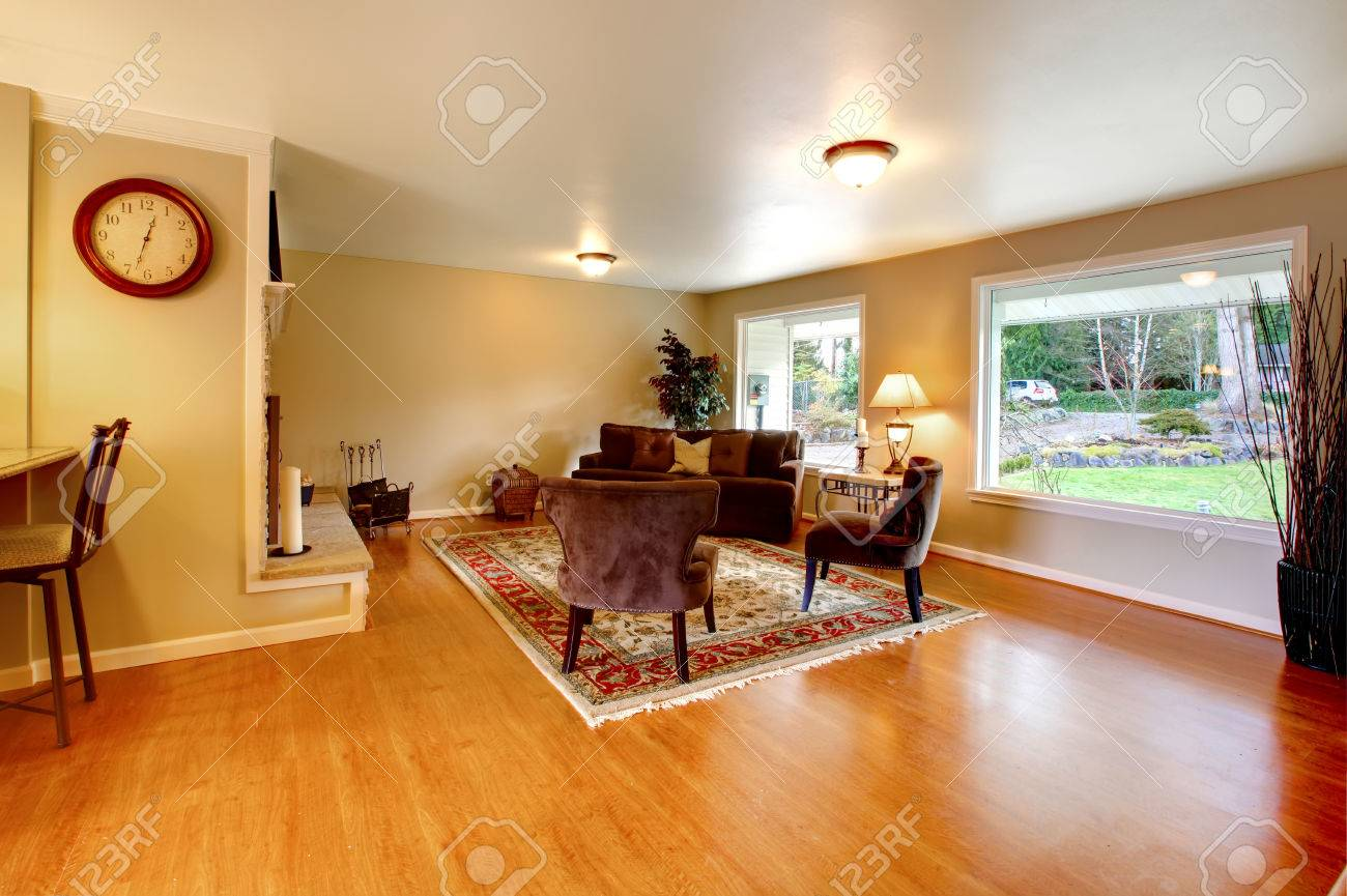 Elegant furnished living room with wide windows and hardwood floor brown velvet couch with chairs