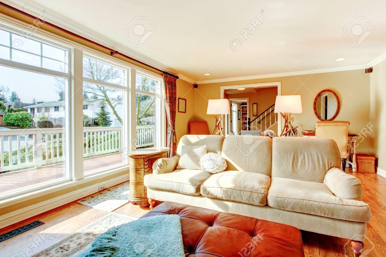 Lumineux couleurs chaudes salon avec des meubles rustiques et du sol au  ceilign fenêtres