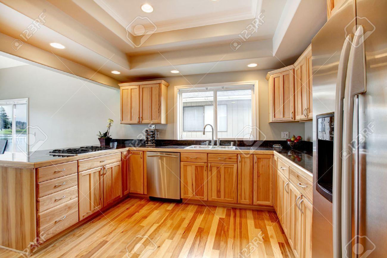 Woode keuken met zwart aanrechtbladen, hardhouten vloer, witte ...