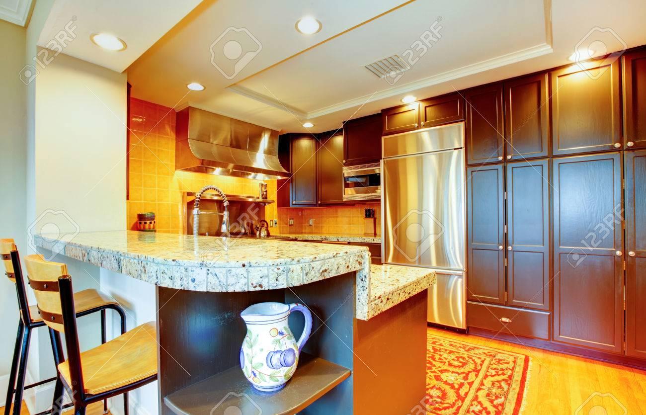 Cuisine à manger avec armoires en bois noir, comptoirs en marbre, appliaces  en acier et tabourets de bar en bois