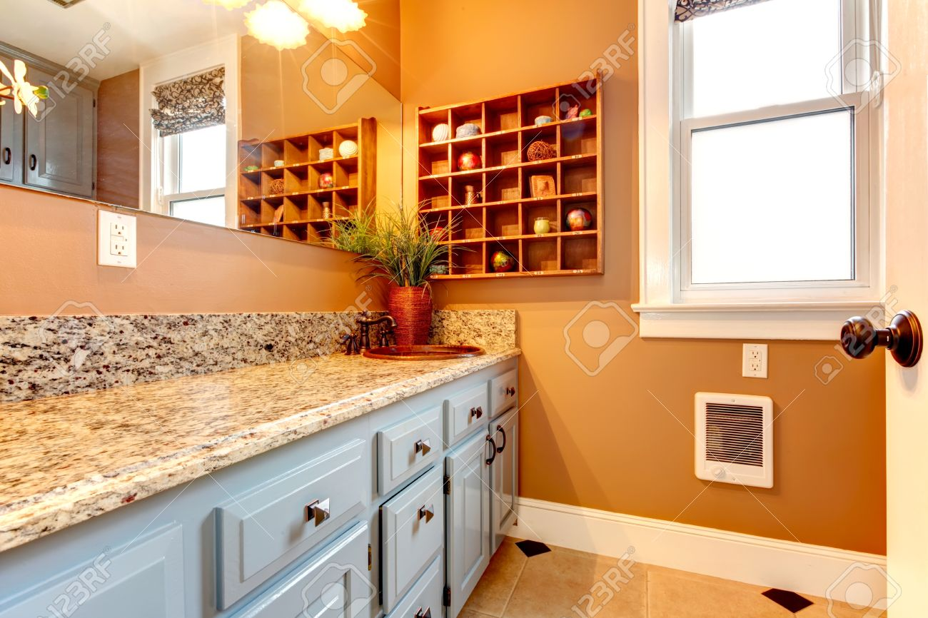 Salle de bains avec armoires modernes blanc, marbre comptoir, robinet de  fer rustique et étagères en bois