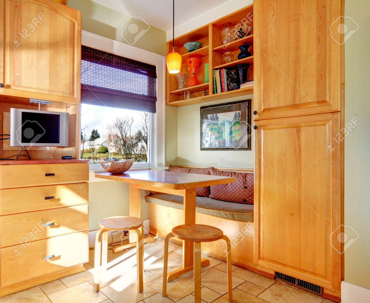 Esquina de la habitación Cocina con muebles de color marrón claro, pequeña  mesa y taburetes.