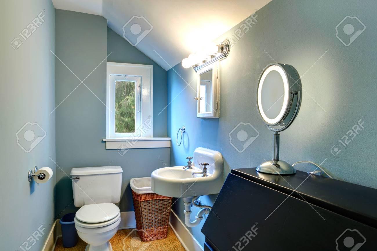 Petite salle de bains avec mur bleu, plafond voûté blanc et le sol jaune