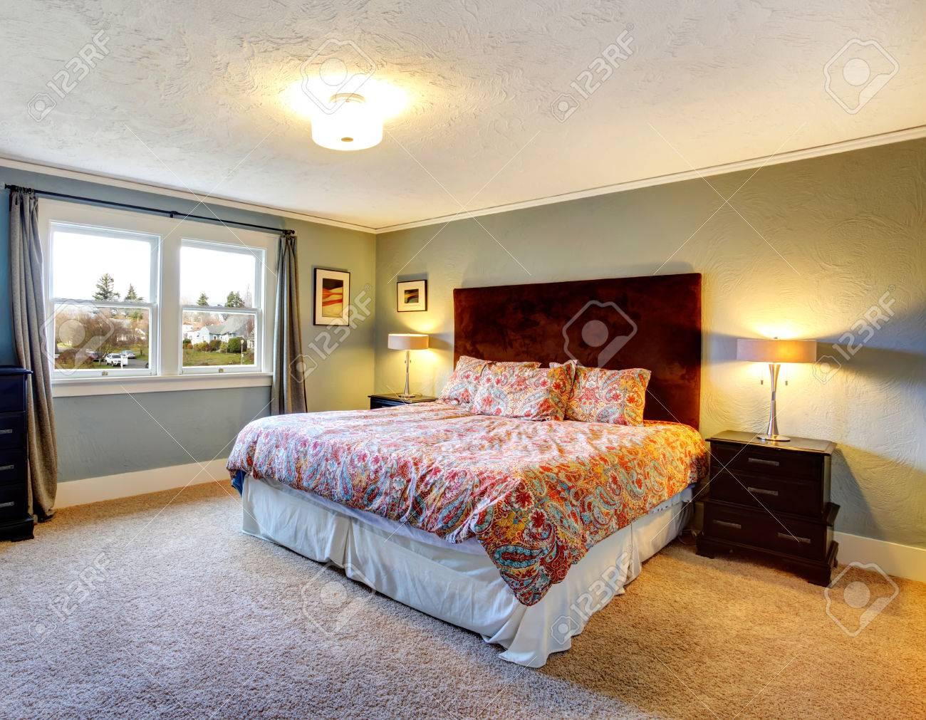 Blu lumière chambre avec moquette beige, tables de chevet en bois noir et  queen rouge tête de lit