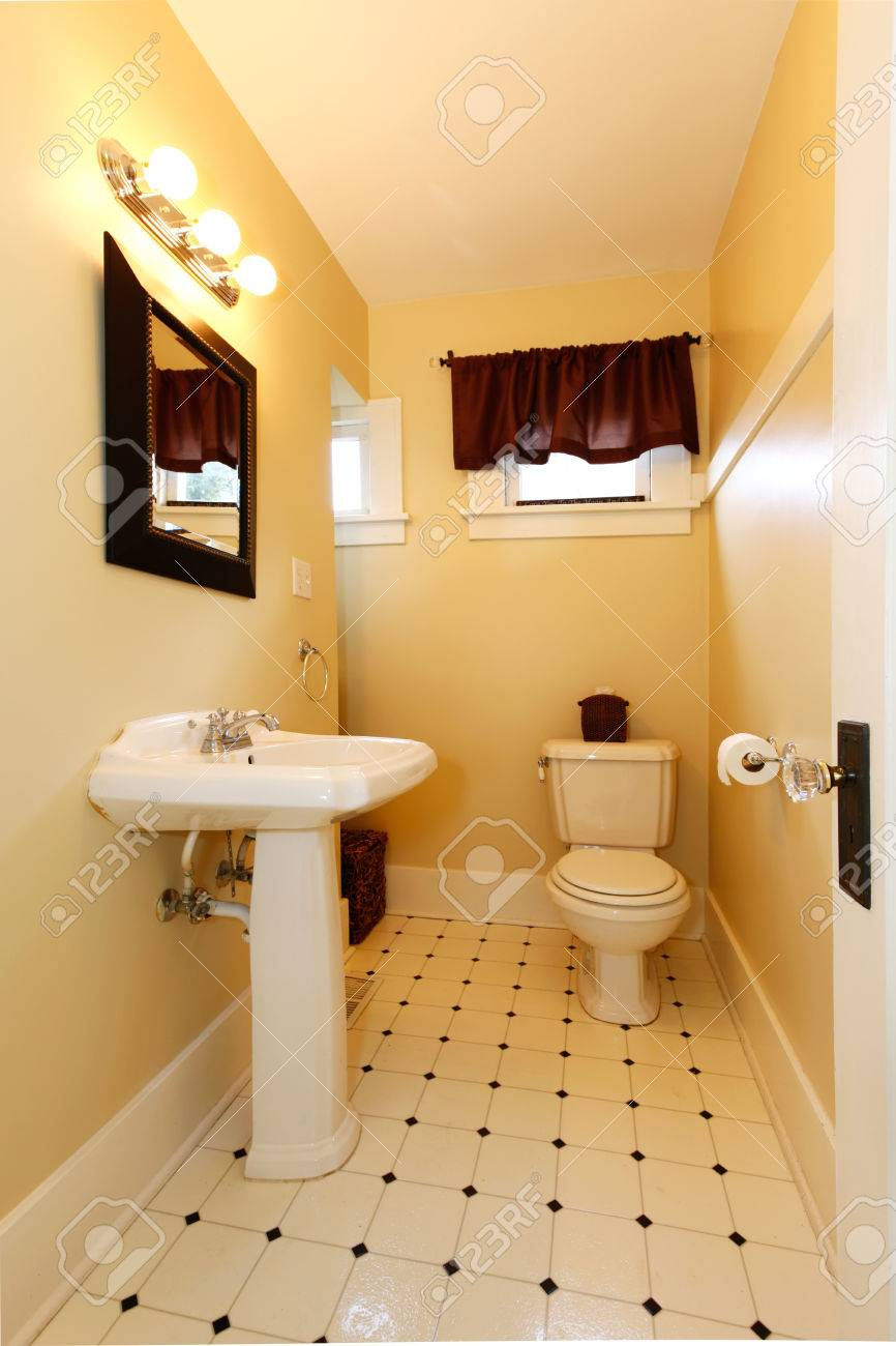 Salle de bain jaune avec carrelage conçu, miroir cadre en bois et des  rideaux bruns