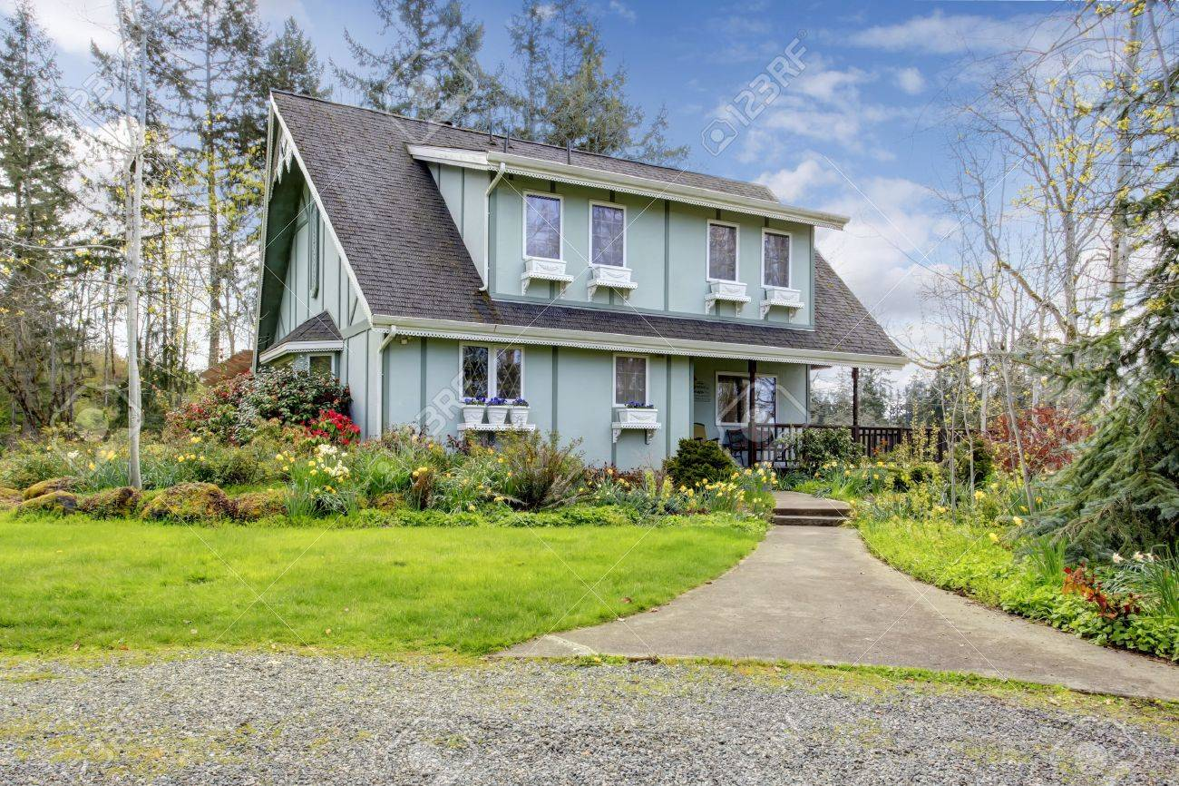 big farmhouse with beautiful flowerbed concrete walkway and