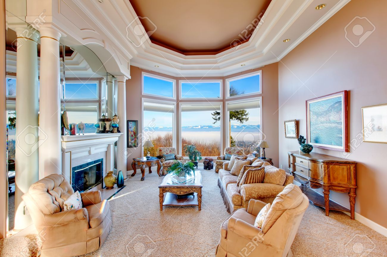 RIch Furnished Living Room With Coffered Ceiling And Colomns.  Floor To Ceiling Angled