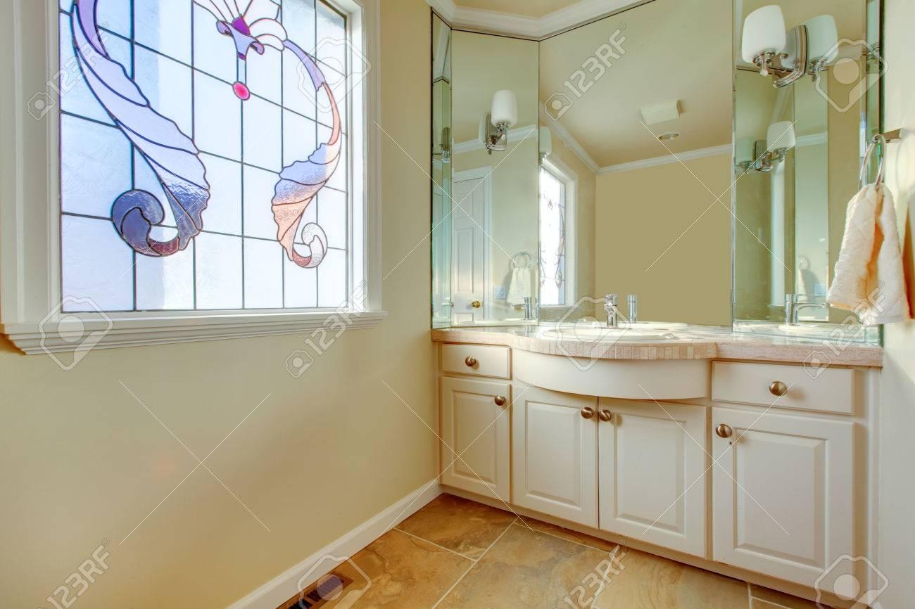 Kleines bad mit beige fliesen, elfenbein schränke, große spiegel ...