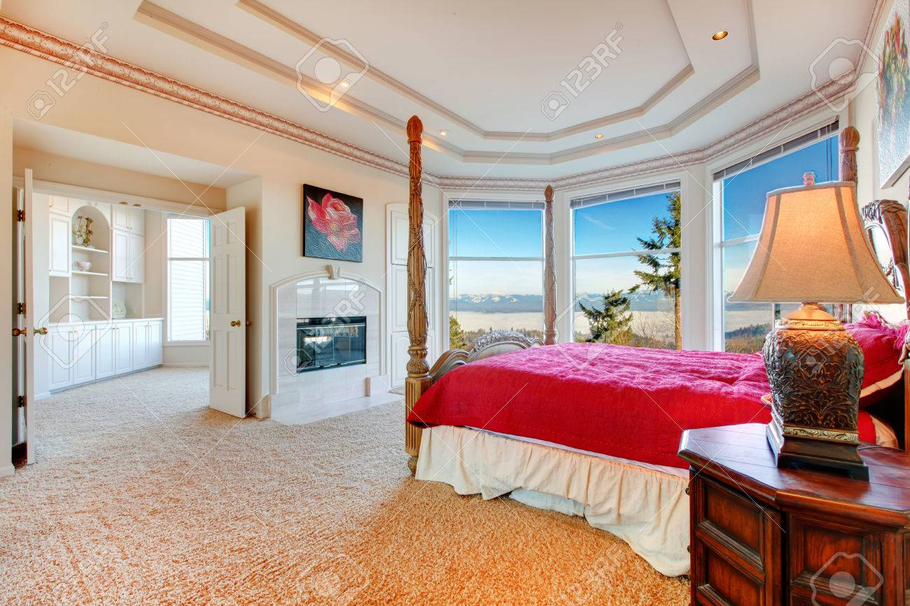 Stunning Luxury Master Bedroom With Rich Bedroom Furniture And Amazing  Angled Glass Wall Overlooking Picturesque View