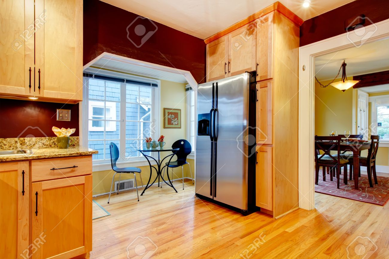 Cozy Kitchen With Burgundy Walls And Light Wood Cabinets. Open To Bright  Dining Area Stock