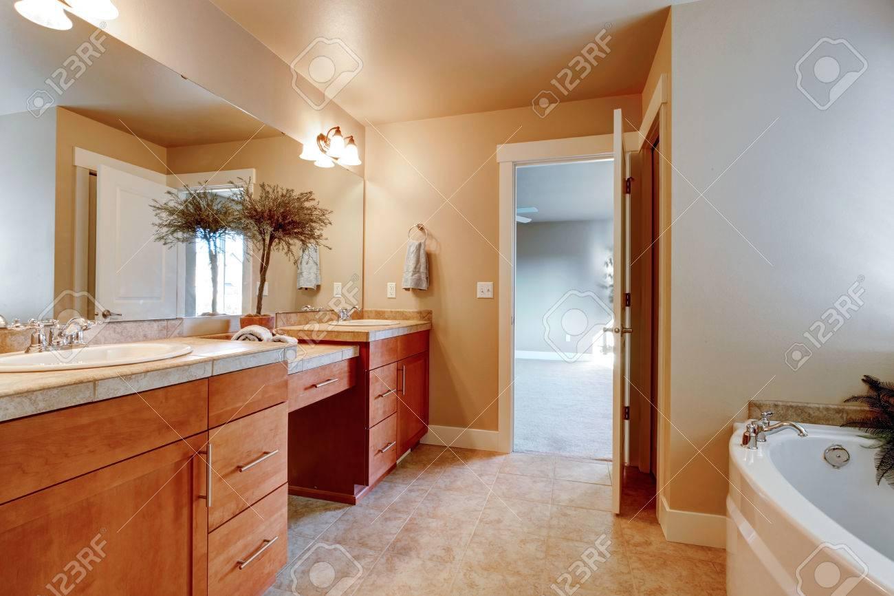 Ivoire salle de bain avec armoires de rangement en bois, carrelage beige.  Décoré avec pot en céramique avec l\'arbre sec