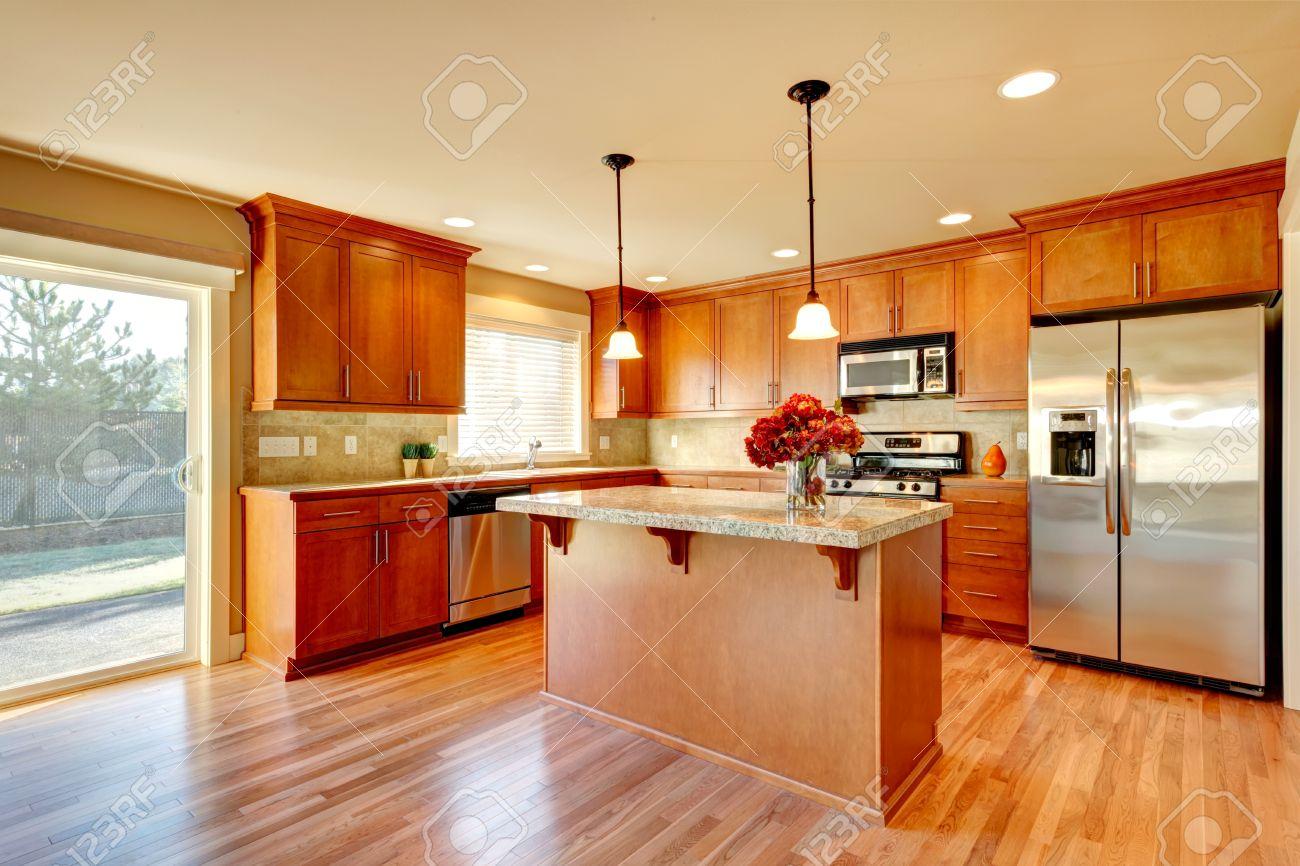 Helle küche mit holzboden, holz schränke, moderne stahlgeräte und ...