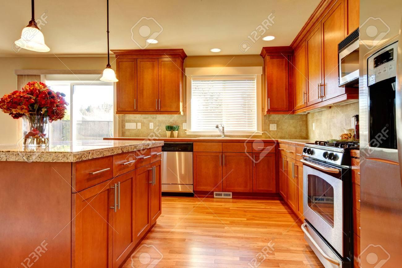 Lichte keuken met hardhouten vloer, houten kasten, moderne stalen ...