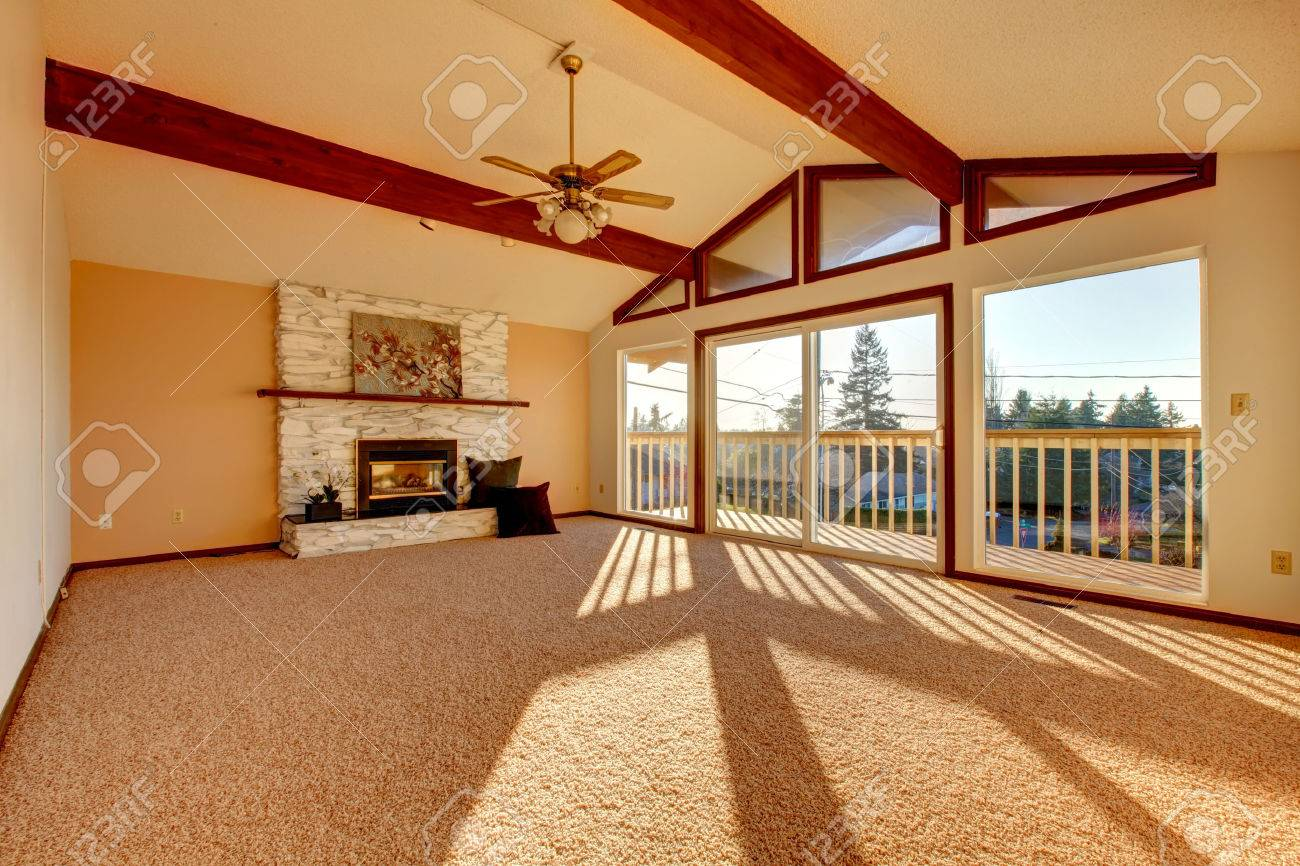living room with vaulted ceiling and beams stoned background