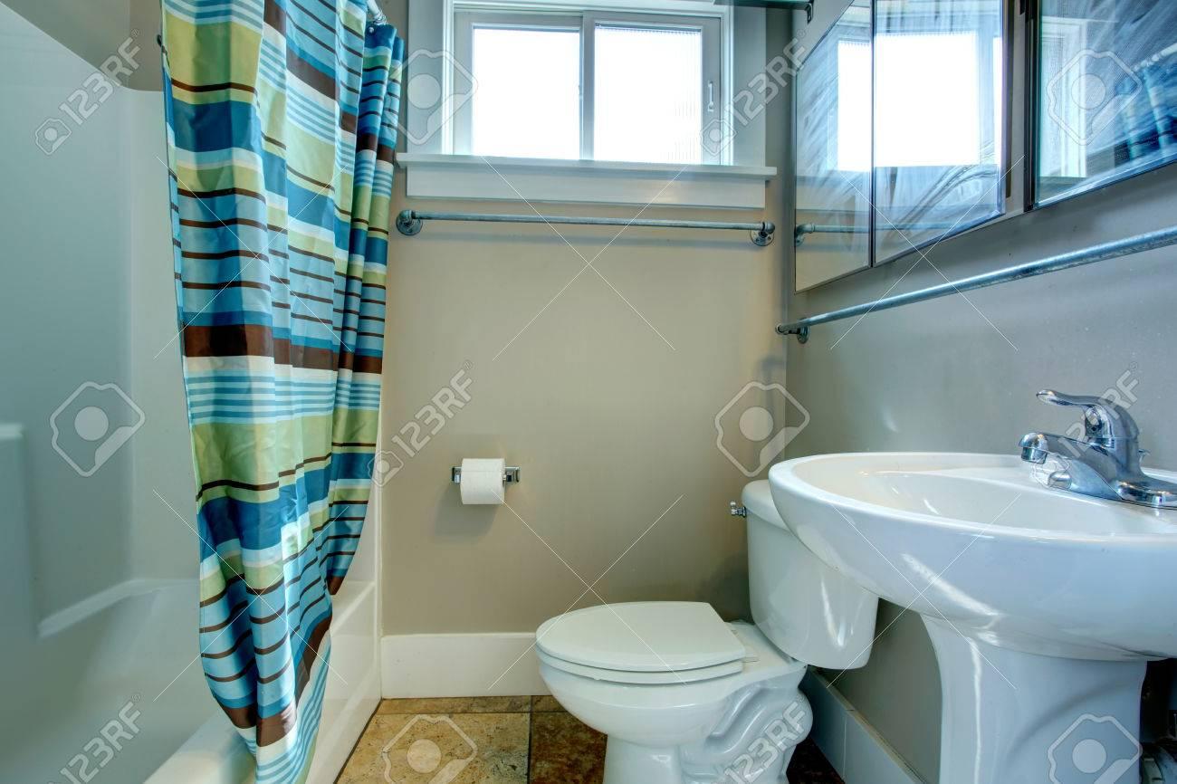 Salle de bain de couleur grise avec carrelage brun, rideaux à rayures  multiples