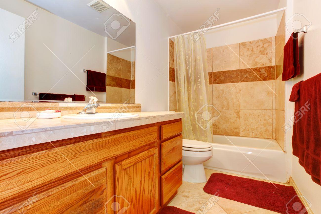 Salle de bain beige avec carrelage, armoires en bois, serviettes rouges,  doux tapis rouge et de voir à travers les rideaux
