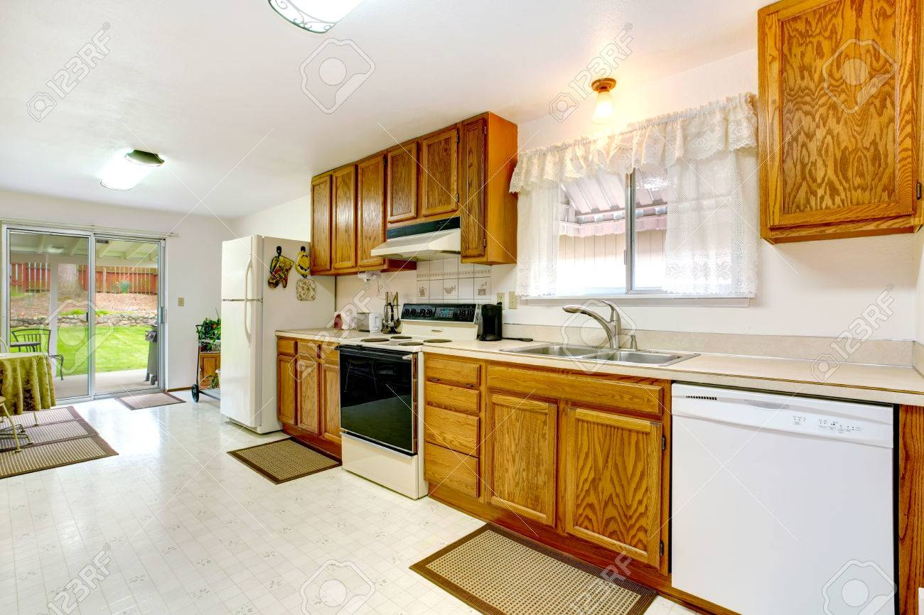 Bright kitchen with wood cabinets, tile floor, white appliances. Small dining area with walkout deck Stock Photo - 25843843