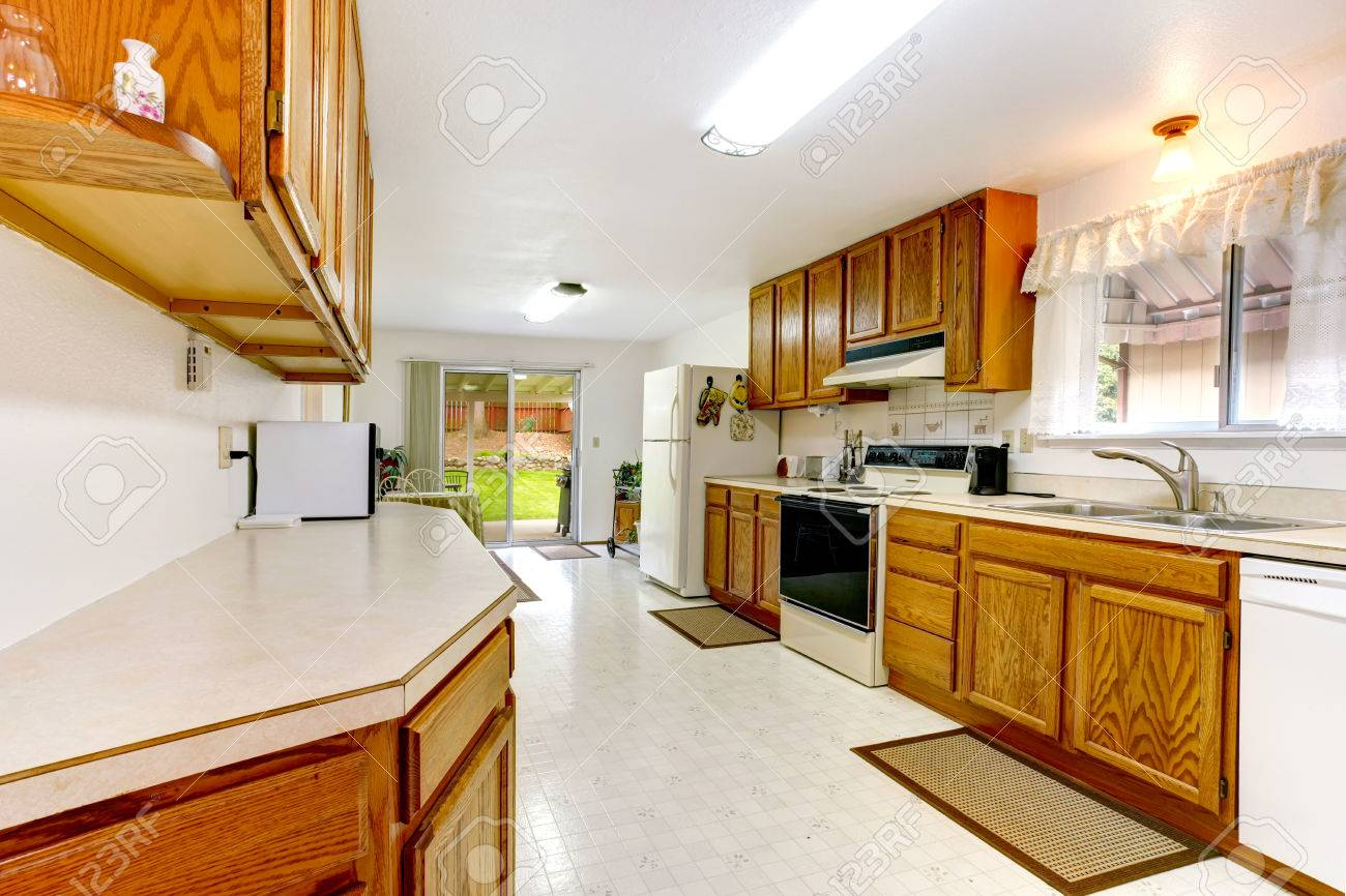 Bright kitchen with wood cabinets, tile floor, white appliances. Small dining area with walkout deck Stock Photo - 25812833