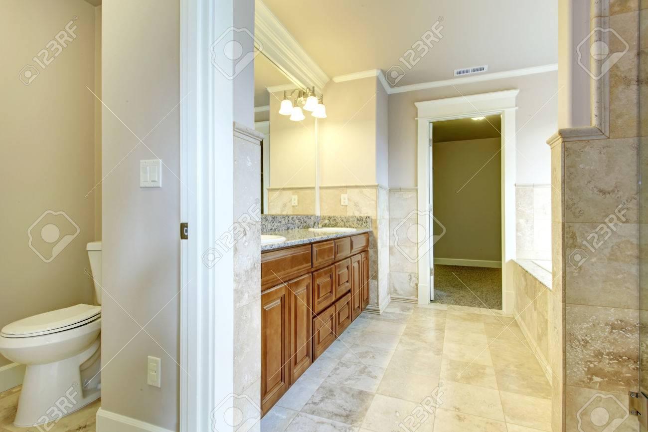 Salle de bain blanc et beige avec armoires en bois, carrelage ...