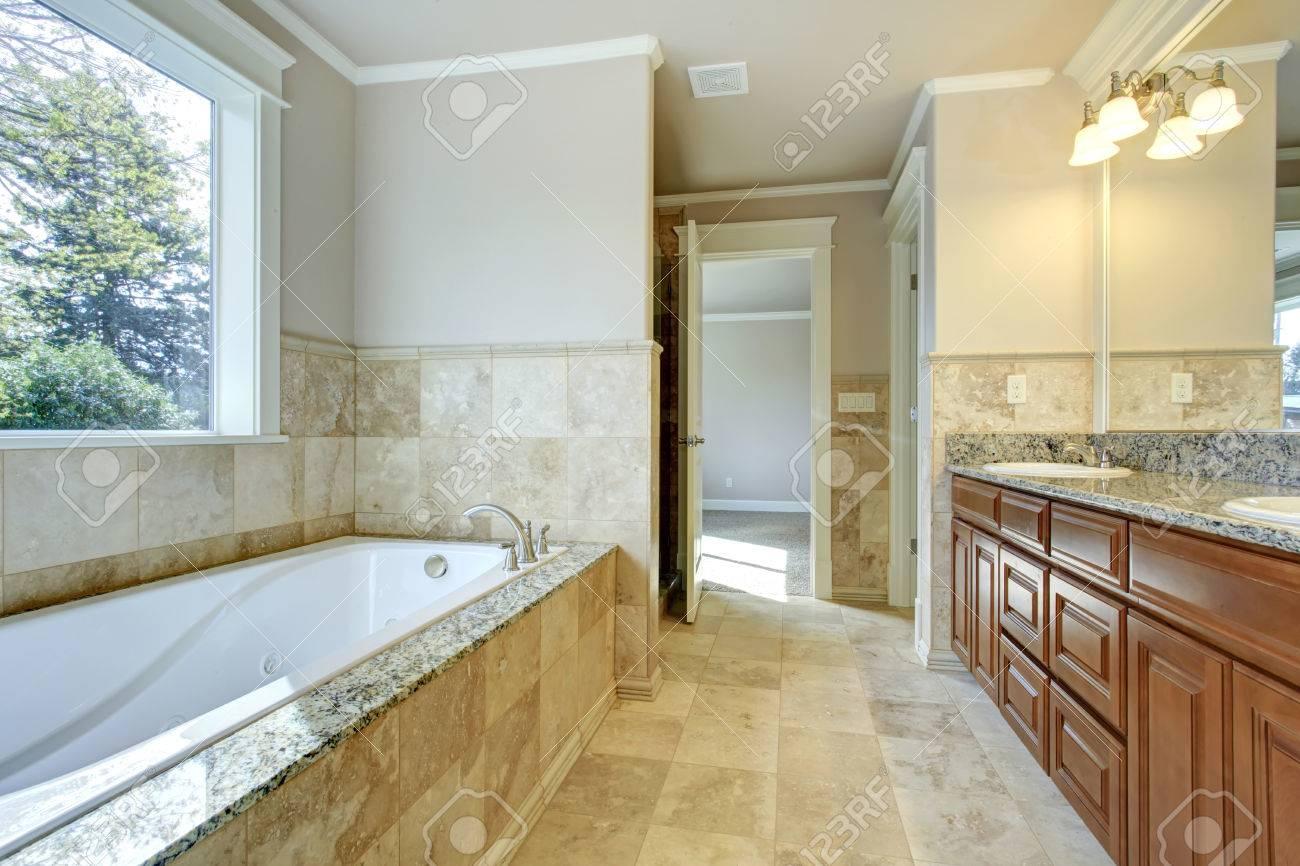 Beige et salle de bains blanc avec carrelage, fenêtre et la combinaison de  rangement en bois