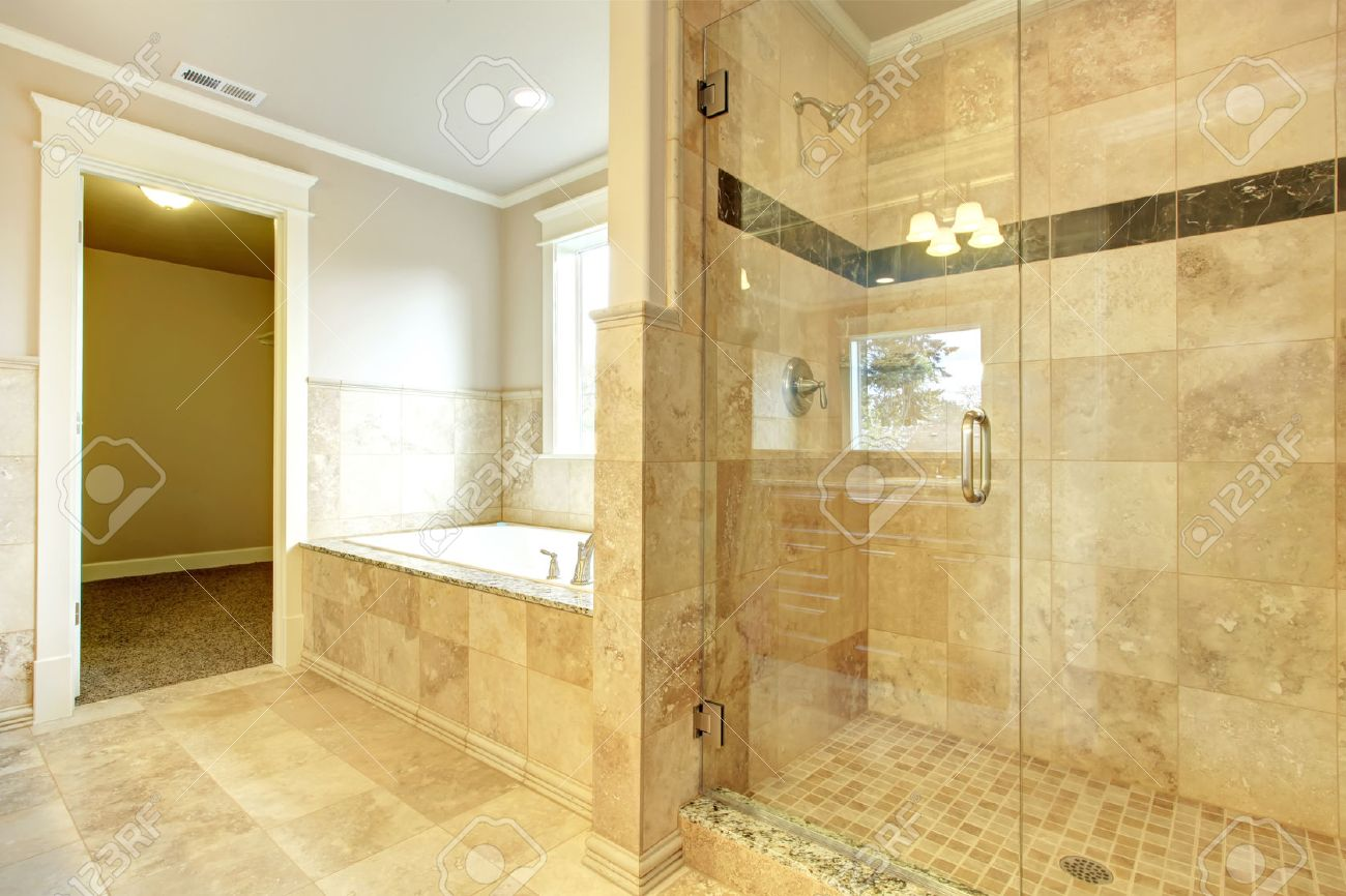 Beight And White Bathroom With White Tub, Beige Tile Floor, Glass Door  Shower Stock