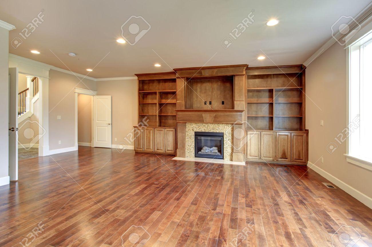 Mur De Rangement Salon salon lumineux avec plancher de bois franc, mur beige, combinaison de  rangement en bois et cheminée en pierre