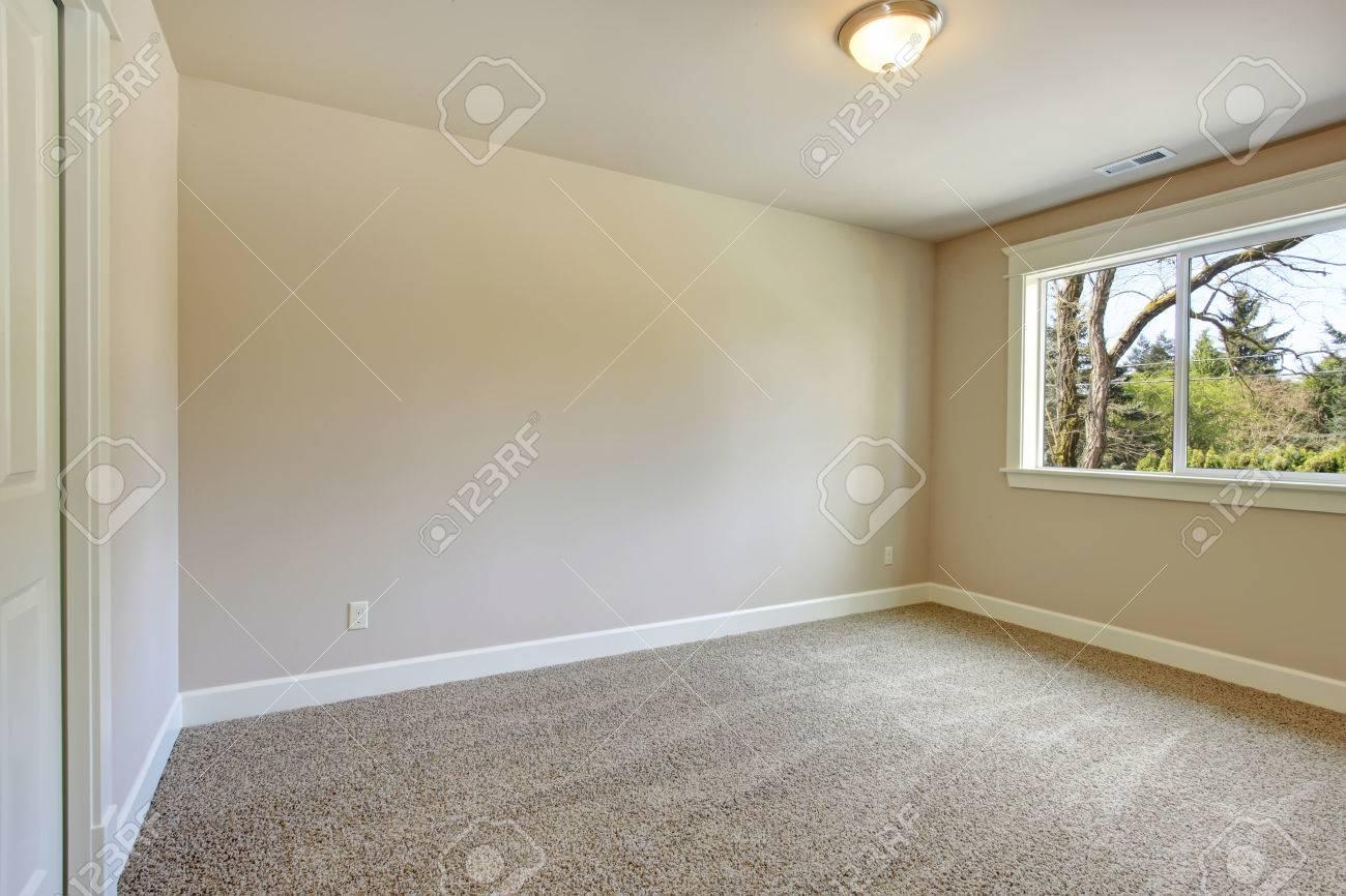 Heldere lege kamer met een raam, beige vloerbedekking en ivoor ...