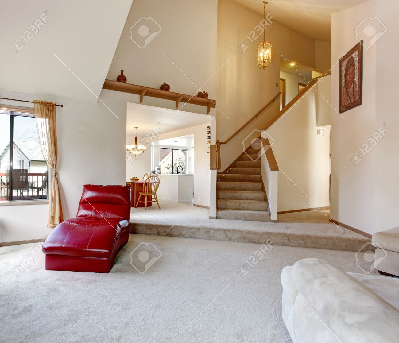 High Vaulted Ceiling Living Room With Hallway And Stairs Open To Dining Kitchen