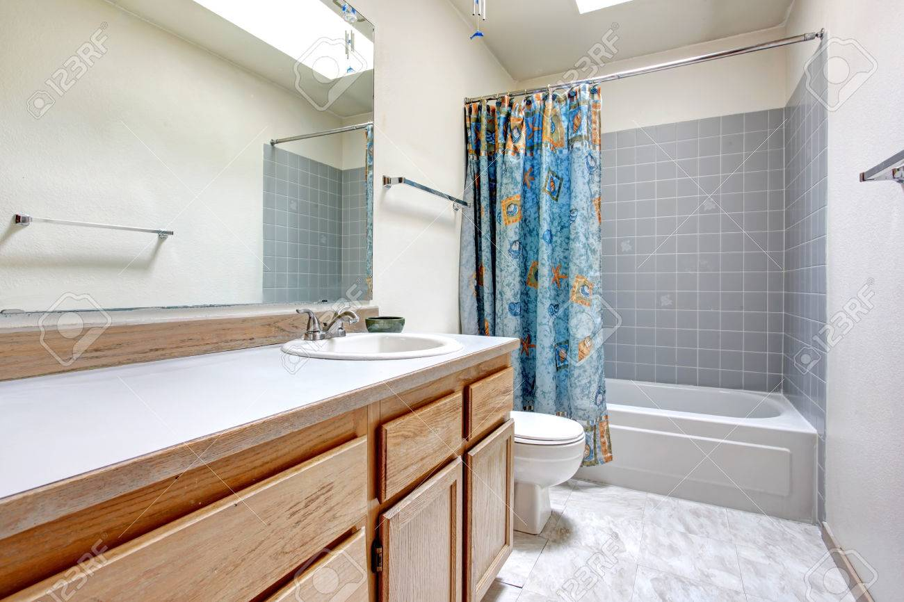 White Bathroom With Wood Cabinets, Tile Floor. Refreshing Blue ...