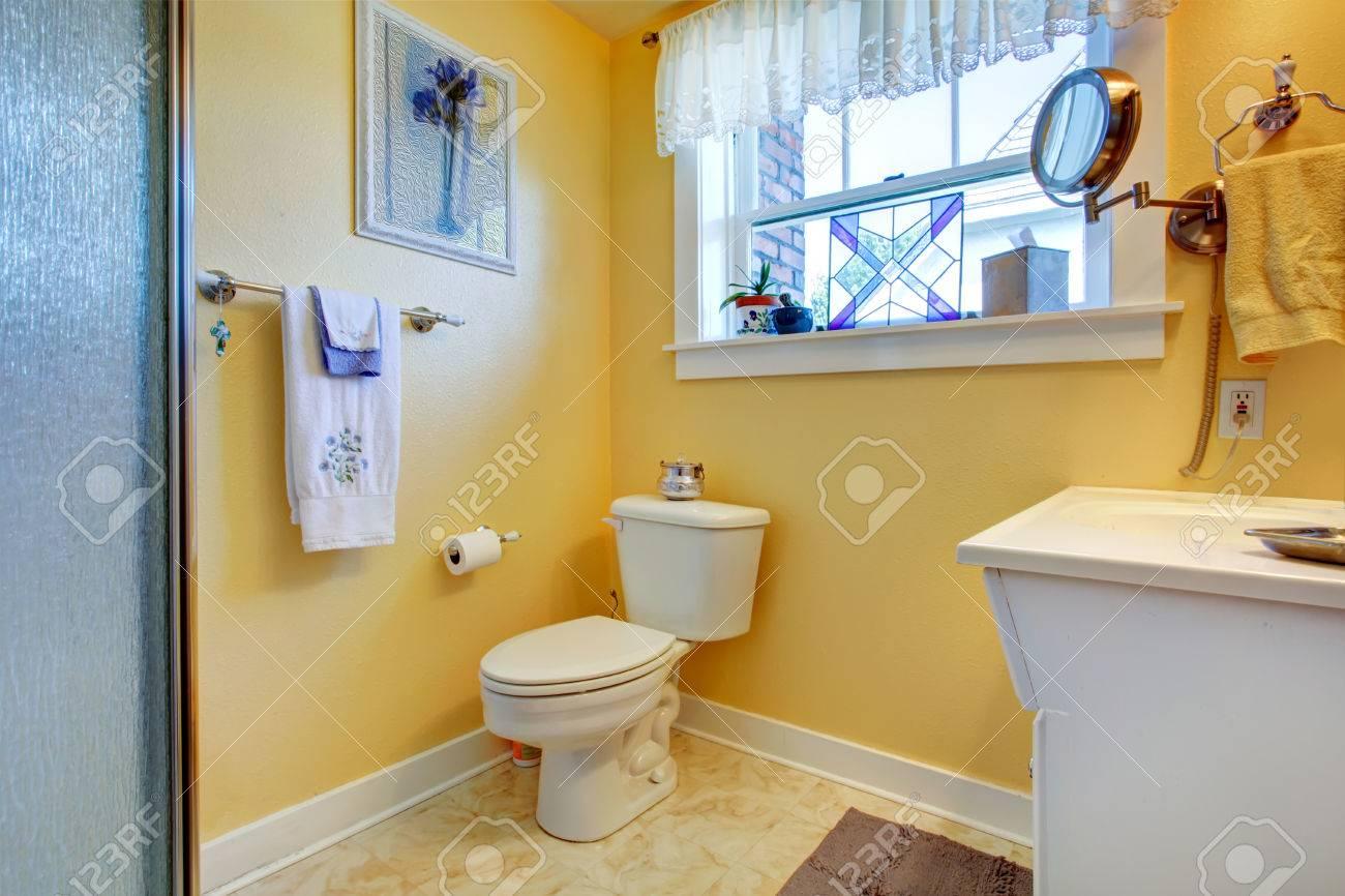 Salle De Bain Jaune Avec Carrelage Beige, Toilette Blanche Et ...