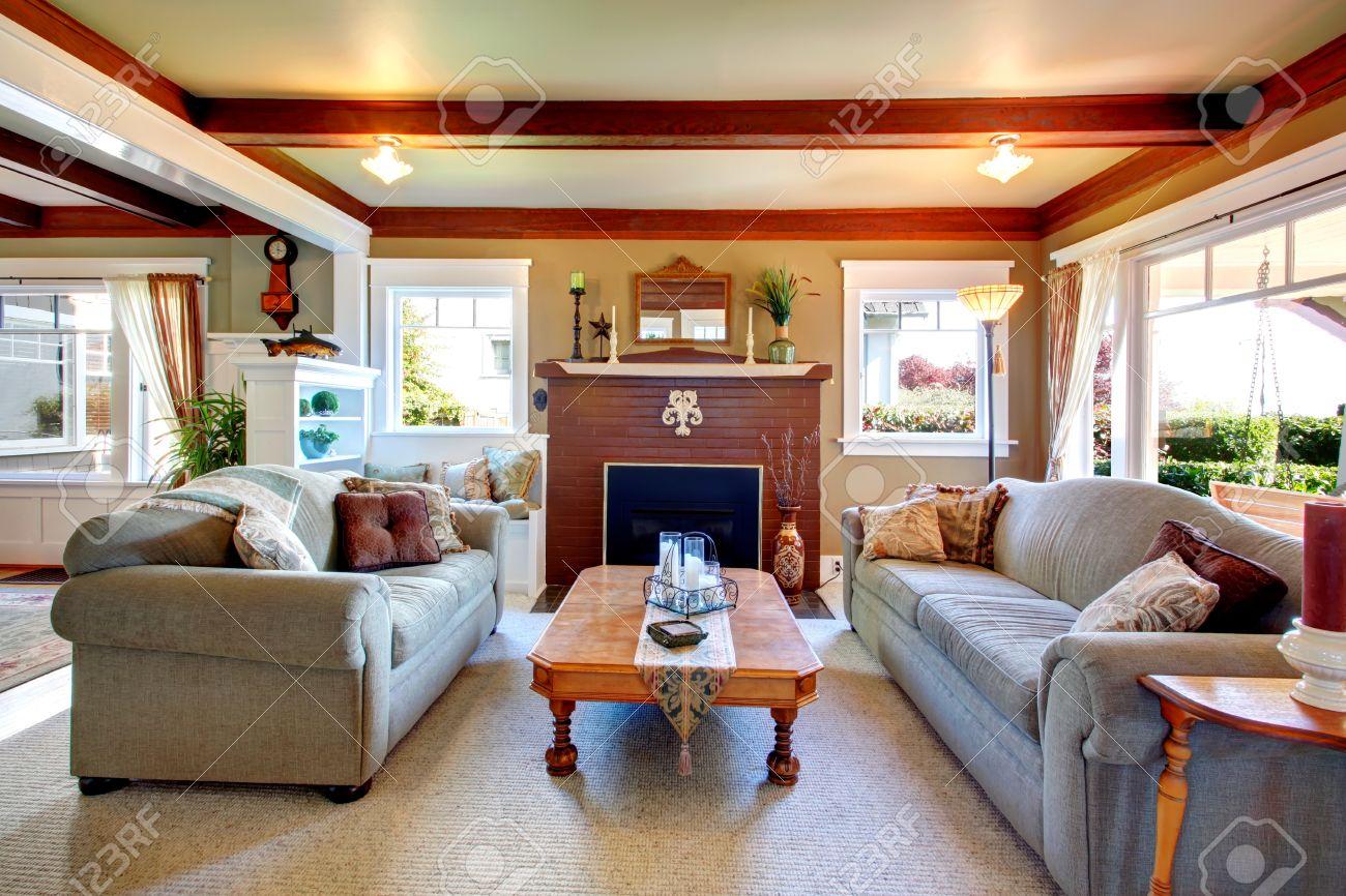 Großes Wohnzimmer Mit Grauem Teppichboden, Deckenbalken, Gesteinigt  Hintergrund Kamin. Wohnzimmer Mit Sofa Und