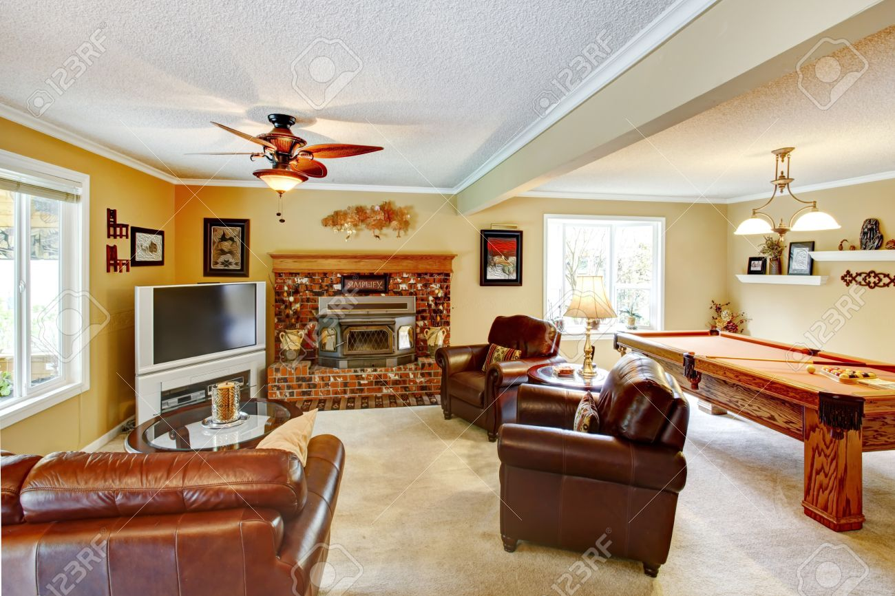 Helles Wohnzimmer Mit Beige Teppichboden Ledercouch Und Sthlen Gemauerten Kamin TV Billardtisch