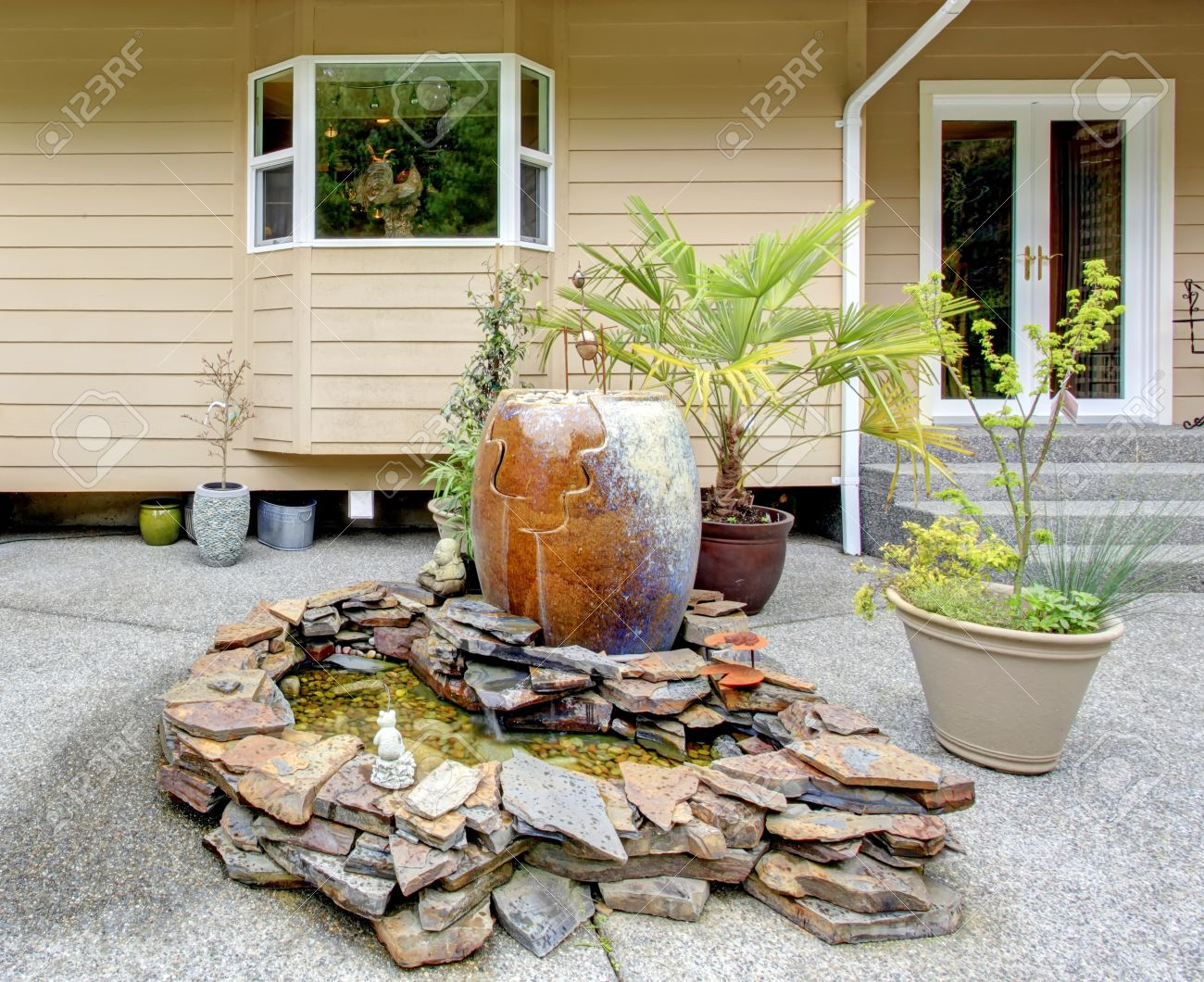backyard porch with concrete floor and decorated rocks with big