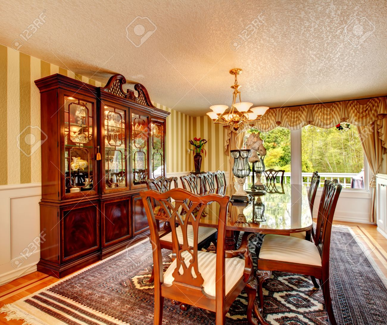 Bright Dining Room With Antique Style Table Set Carved Wood Cabinet Glass Doors