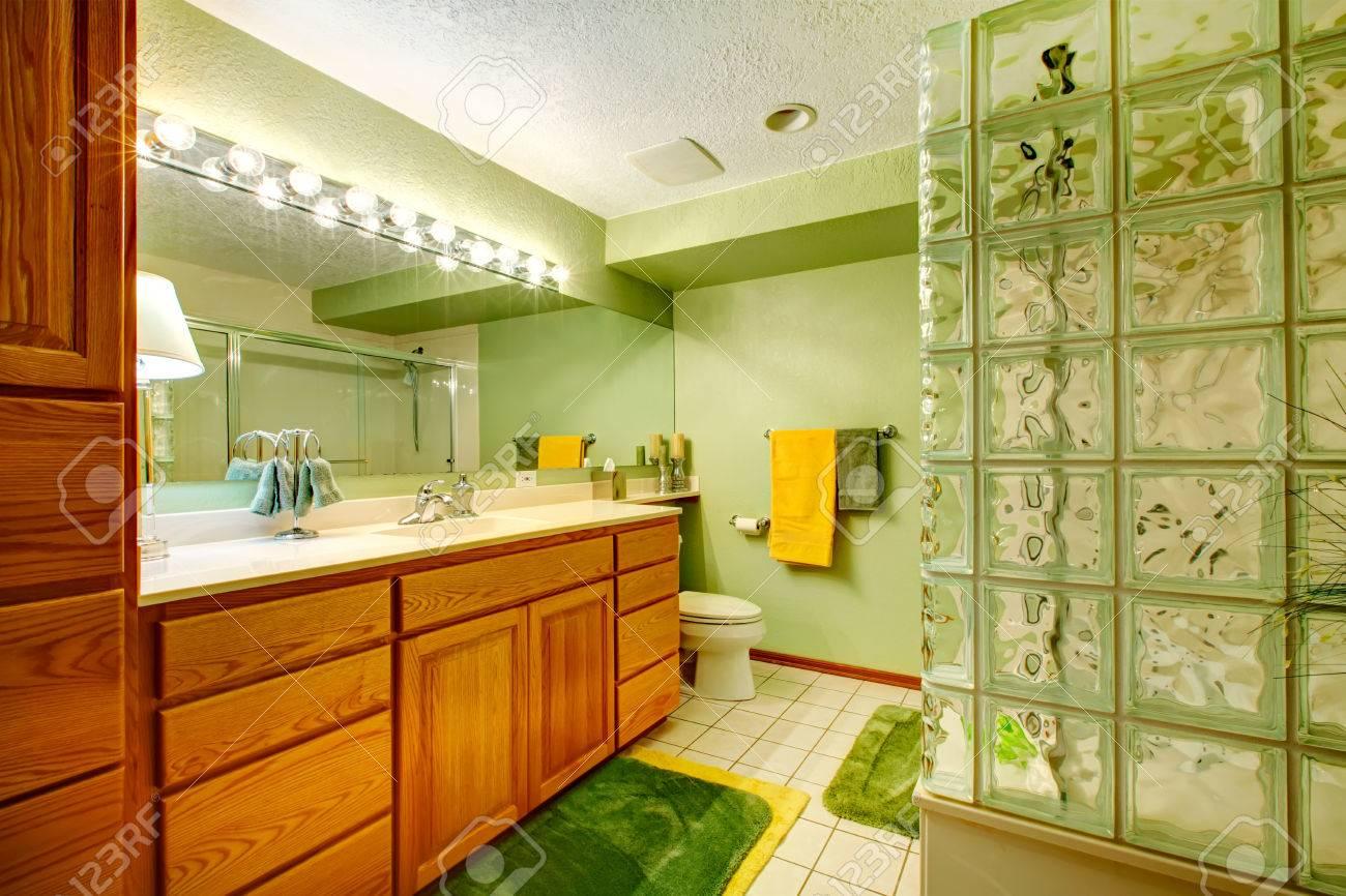 Salle de bains avec des armoires vert brun, carrelage, tapis vert ...