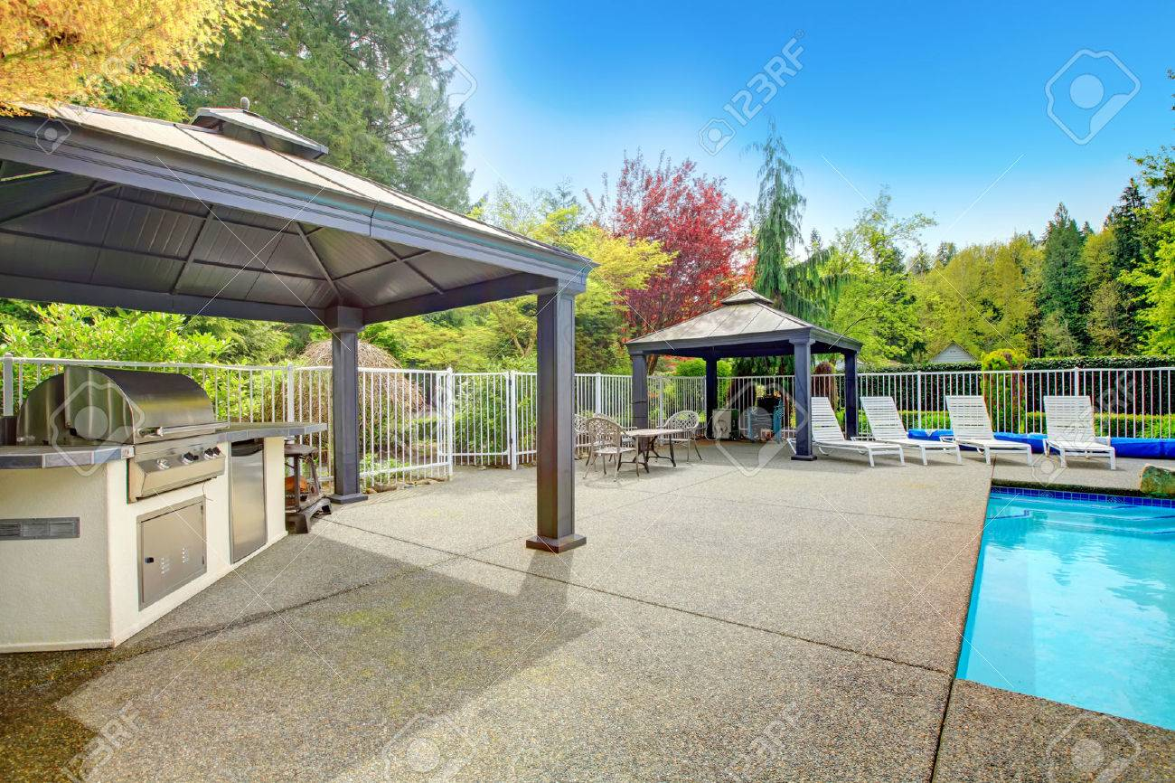 Concrete Floor Patio Area With Barbeque, Table Set, Sun Chairs And Swimming  Pool Stock
