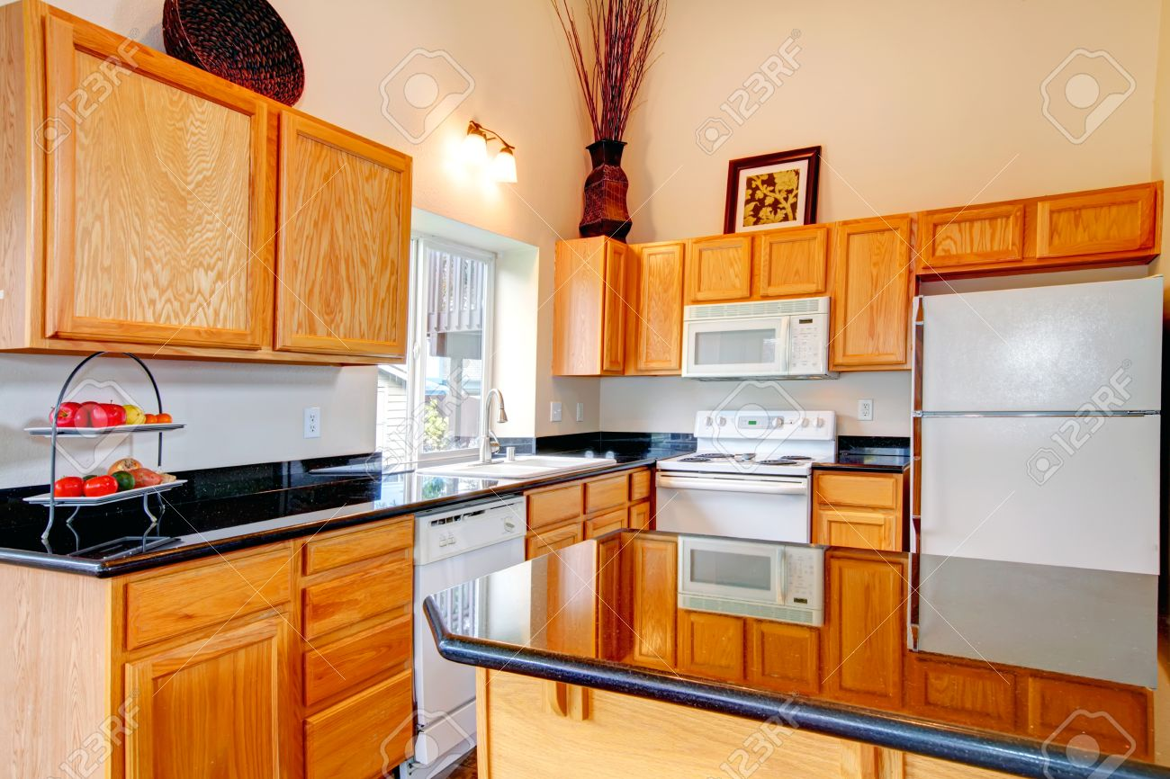Light Brown Cabinets With Black Counter Tops, White Kitchen Appliances.  Room Decorated With Dry