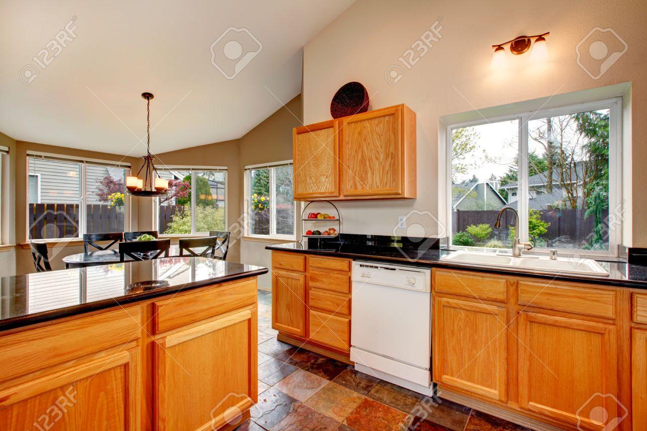 cocina luminosa con suelo de cemento luz gabinetes de color marrn con encimeras negras